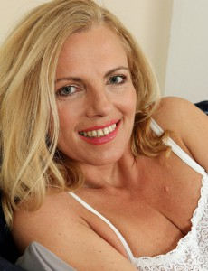 Blond 47 Year Old Beauty Britney Squatting in Front of the Ottoman